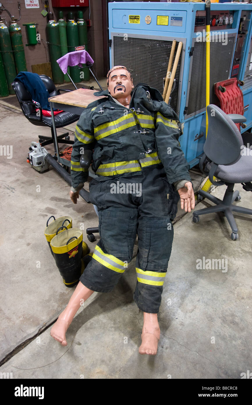 A firefighter training dummy with humorous mustache and hair drawn on wearing a protective fire suit - Stock Image