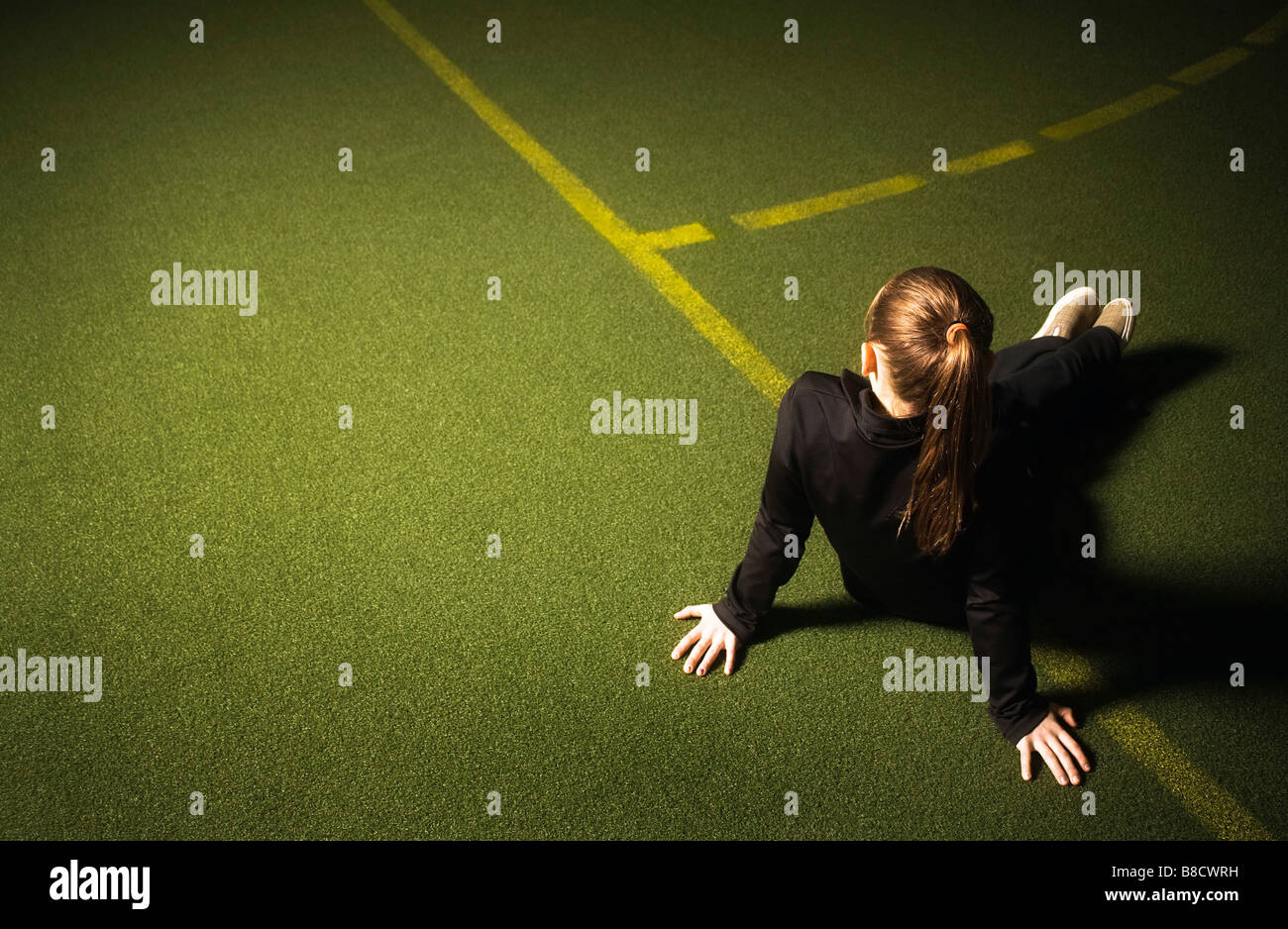 Girl sitting on the sidelines - Stock Image