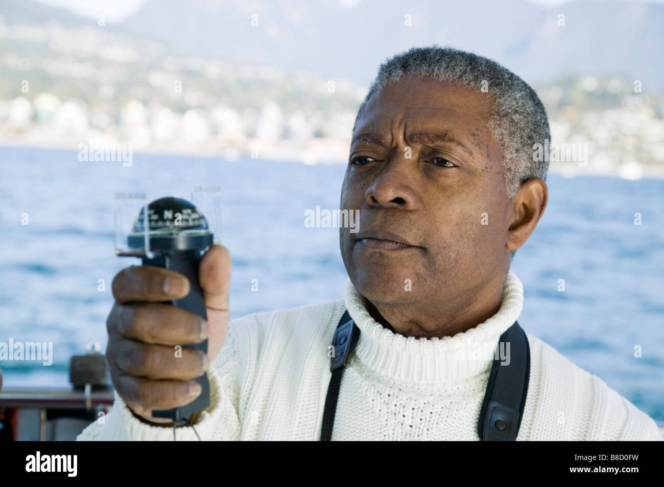 Senior Man Using Sighting Compass his Sailboat, Vancouver Harbour, BC - Stock Image