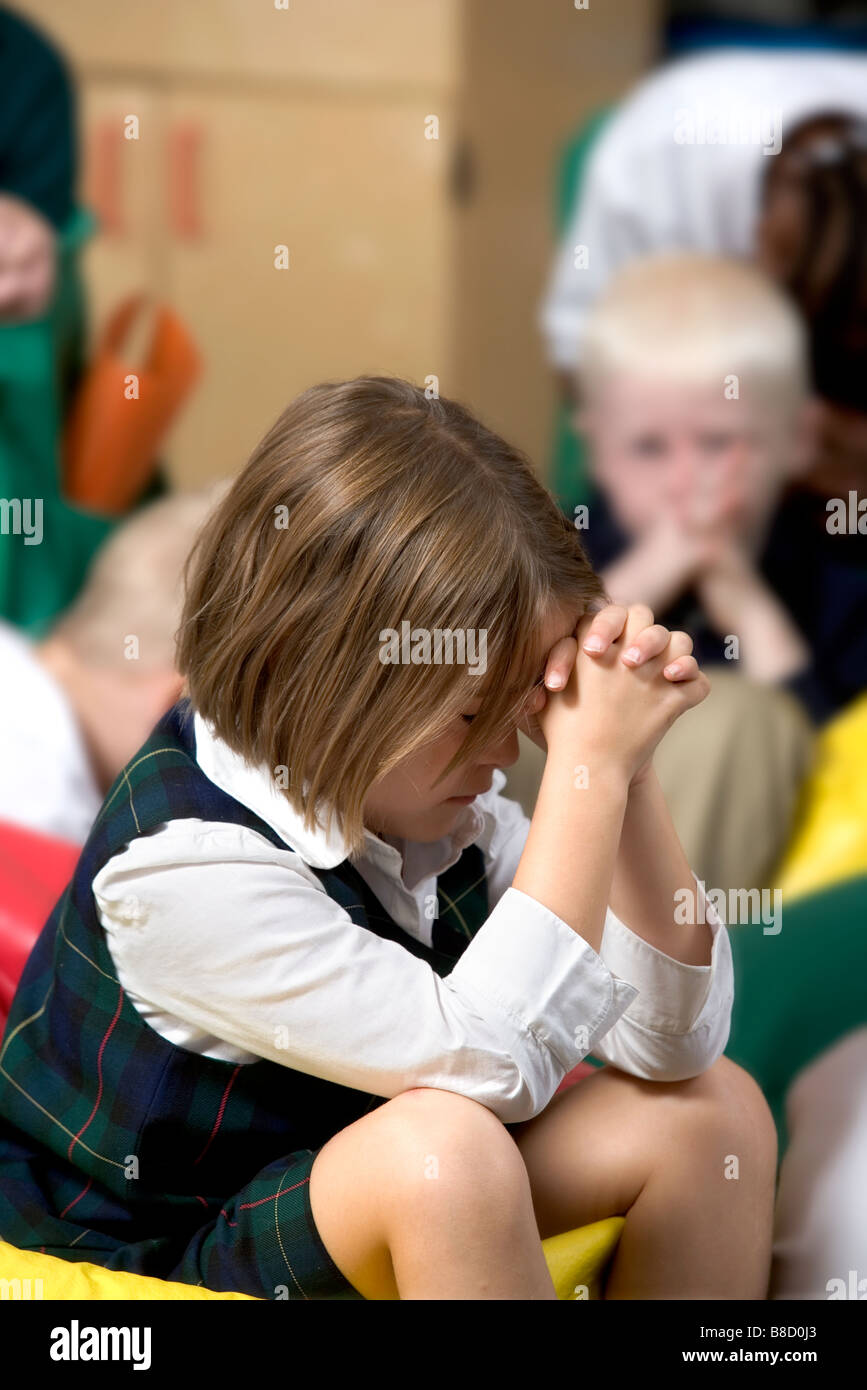 Elementary school girl with her head bowed in prayer. - Stock Image