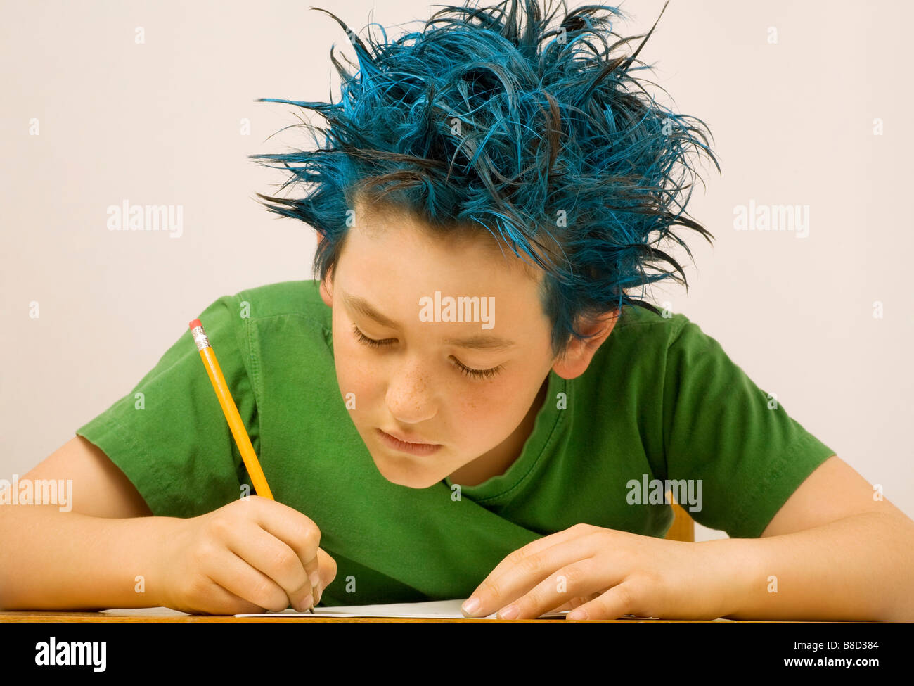 Boy with blue spiked hair writing - Stock Image