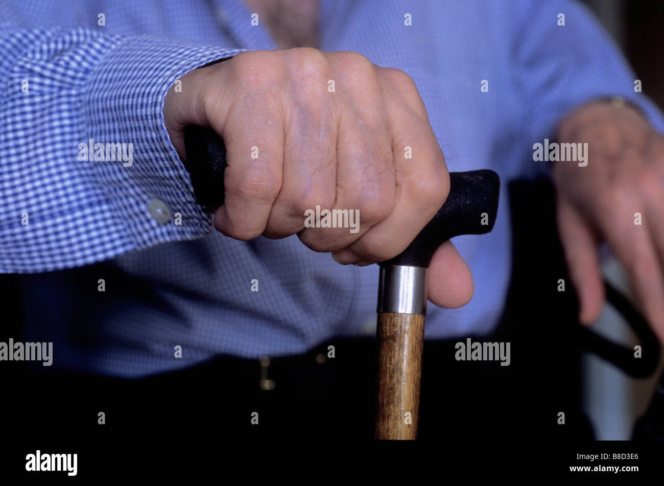 Seated Elderly Man Holding a Cane - Stock Image