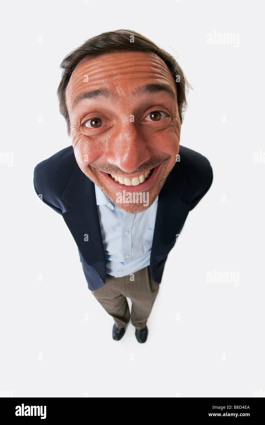 Fish eye lens of a man with a silly grin on white background - Stock Image