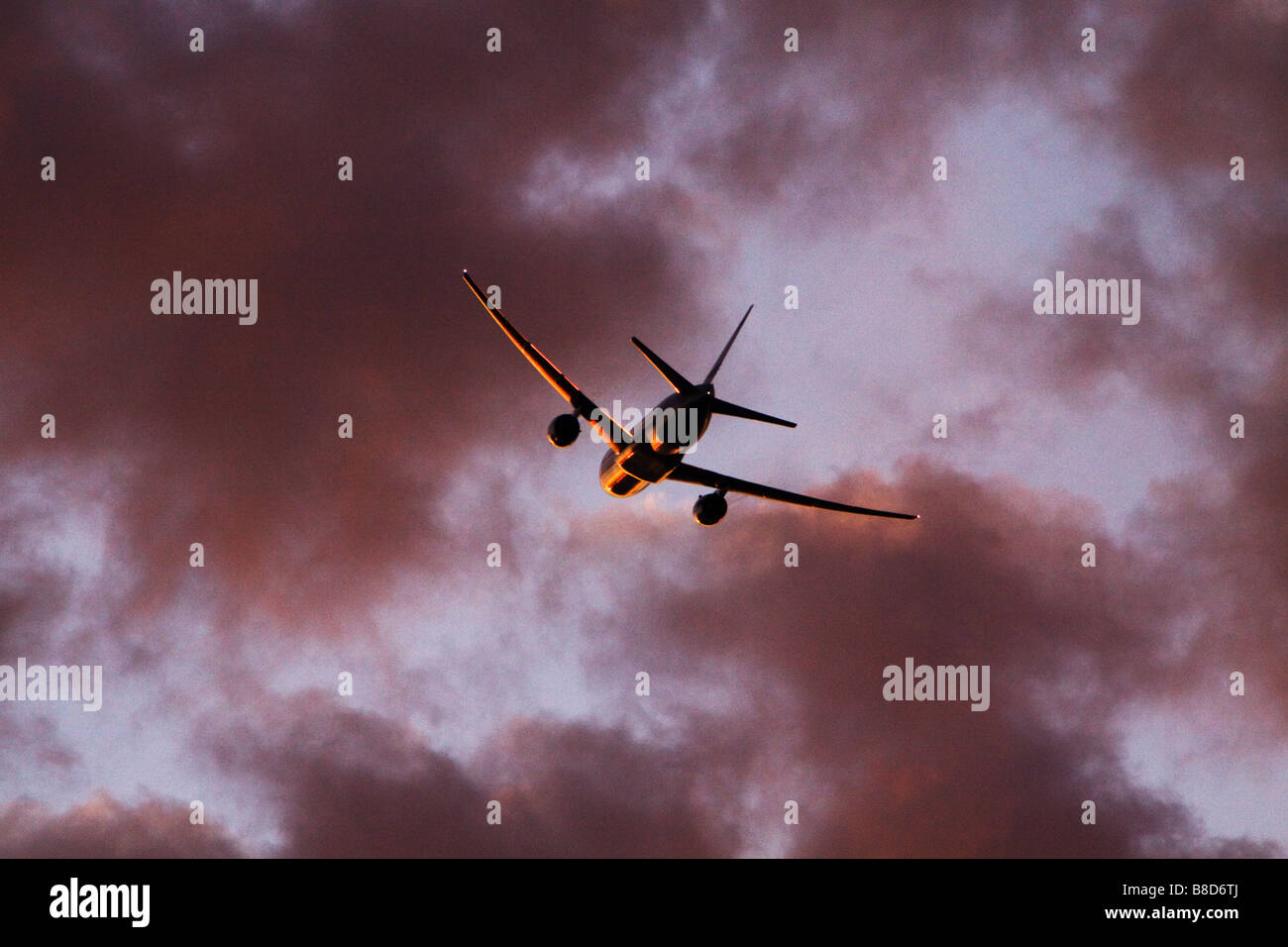 Jet Plane taking off into clouds at sunset with spectacular gold rim lighting. - Stock Image