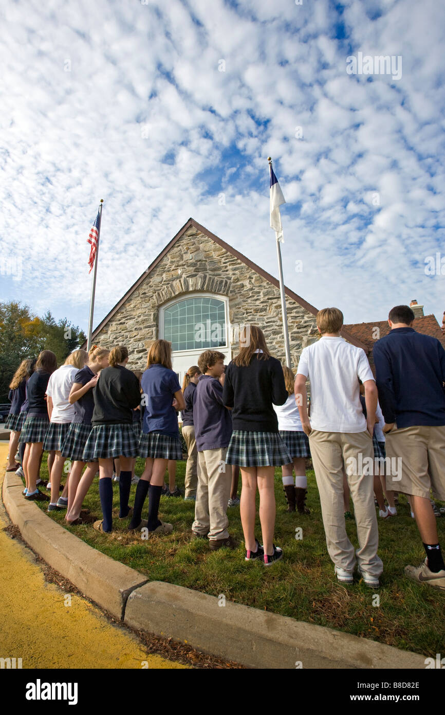 Students gathered around the flagpole at a private school. - Stock Image
