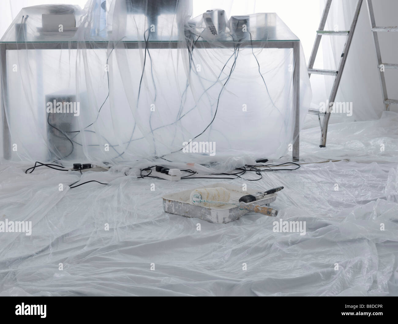 Messy desk with computer and cables covered in dust sheets - Stock Image