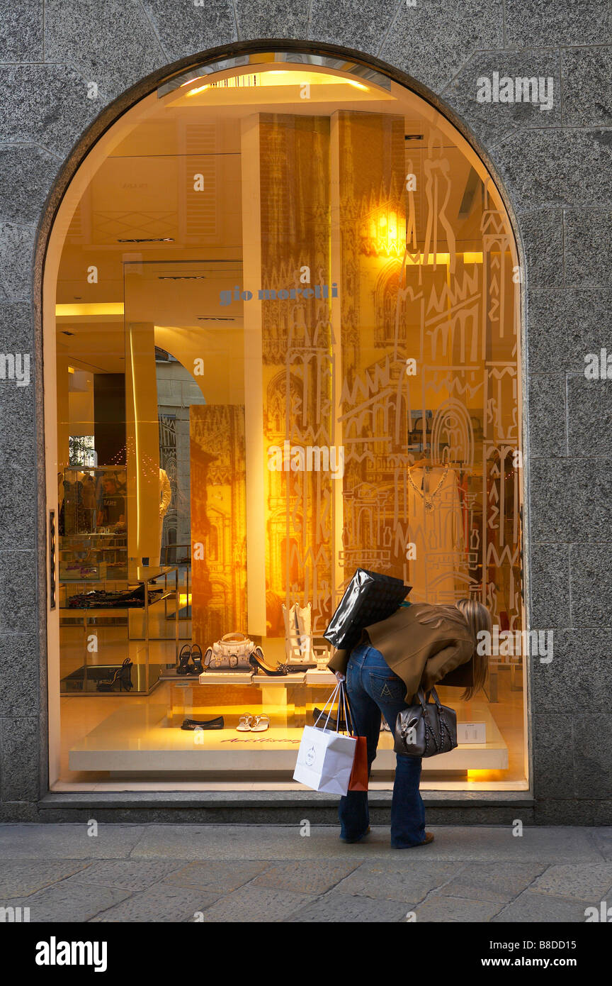 a woman looking at a display in a shop window in the fashion district, Via della Spiga, Milan, Lombardy, Italy. - Stock Image