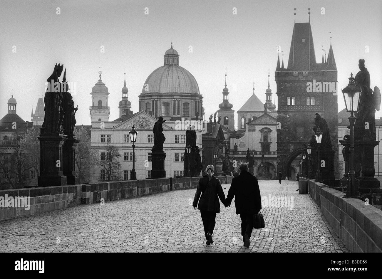 couple walking on the Charles Bridge at dawn, Prague, Czech Republic - Stock Image