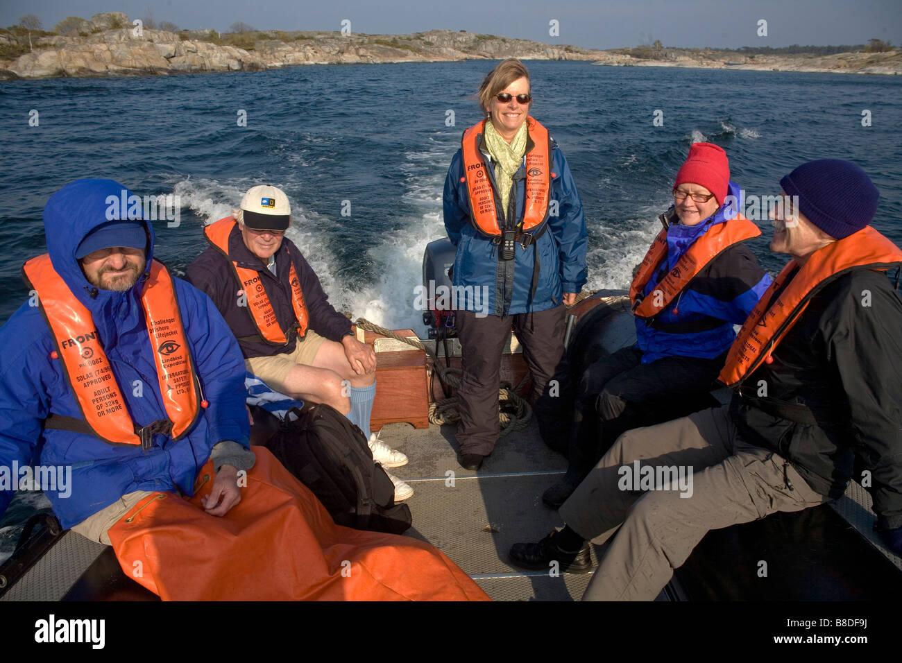 American tourists arriving in zodiac to Bullero island at Swedish Archipelago, Sweden Baltic sea - Stock Image