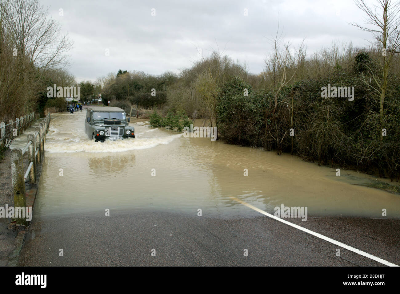 Landrover jeep speeds through flood water in Essex Uk after large amounts of rainfall that flooded rivers and closed - Stock Image