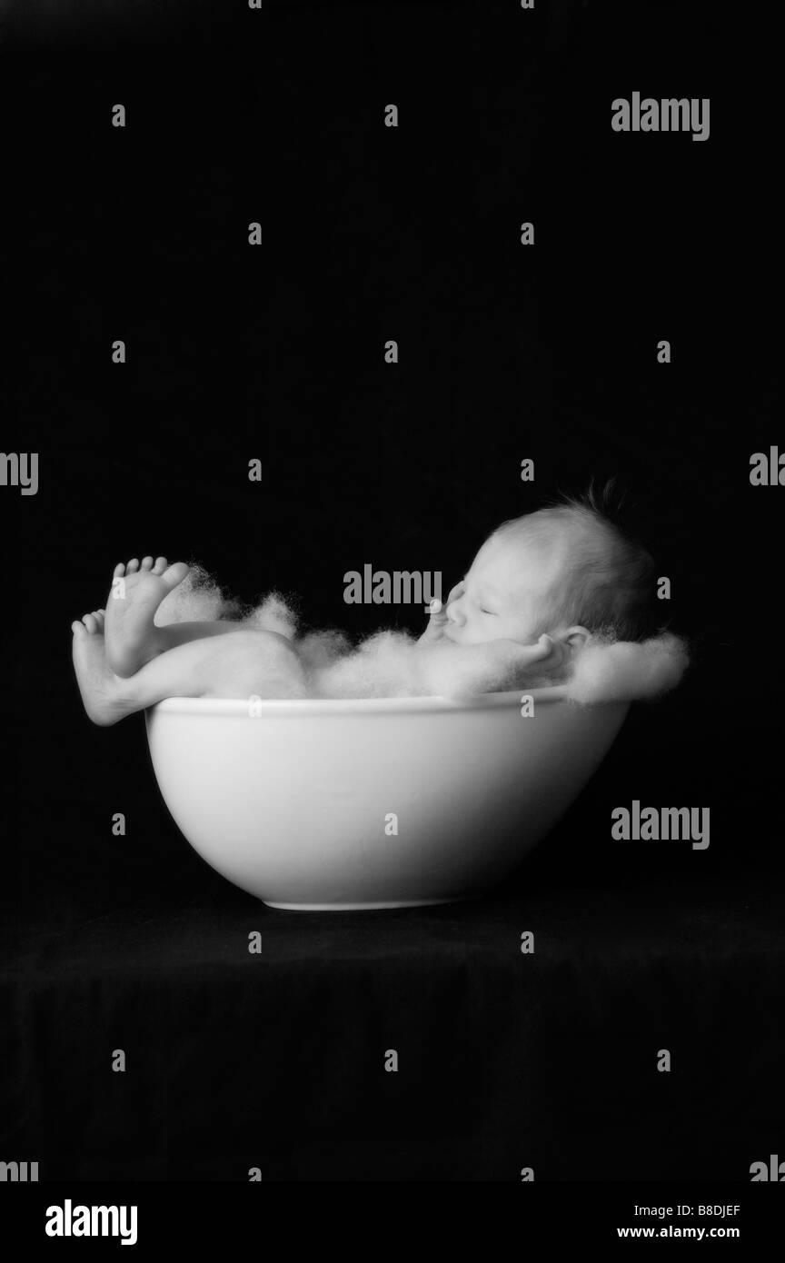 Infant child in bowl, on black background - Stock Image