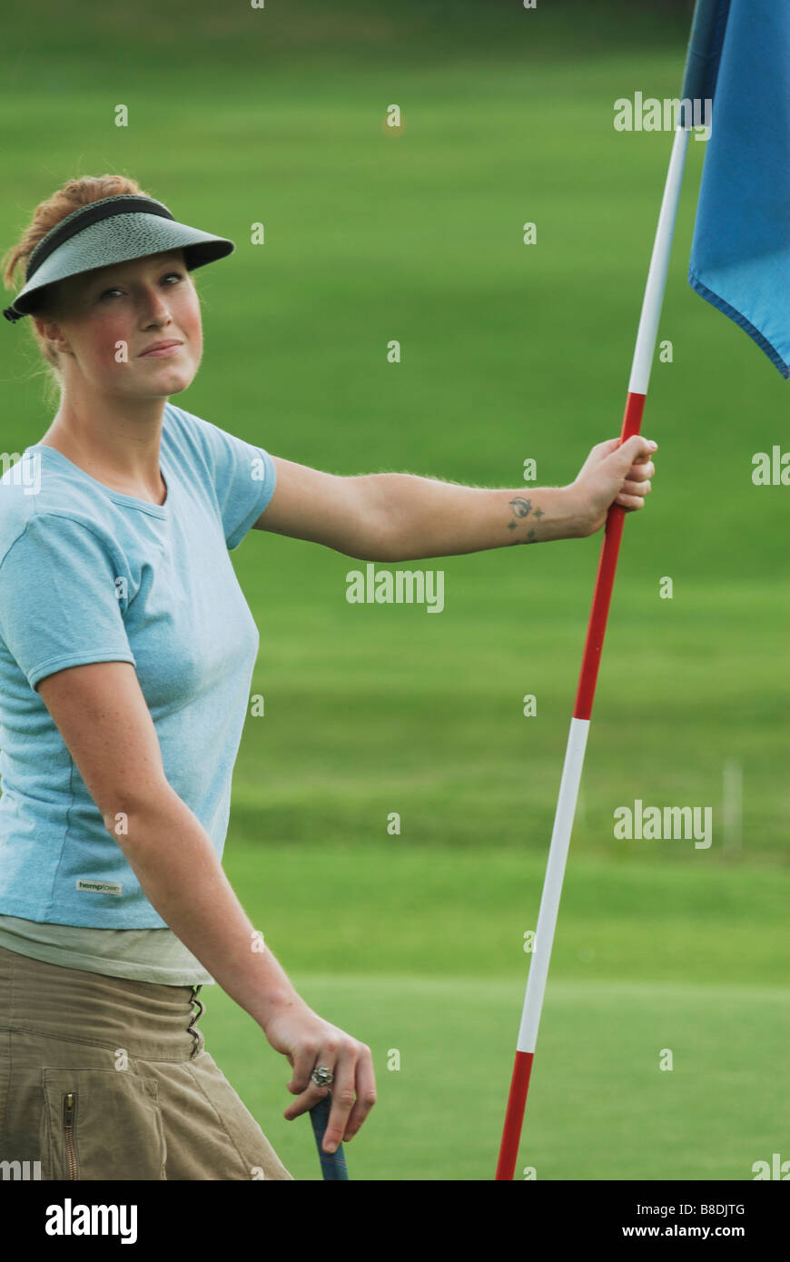 Woman on putting green, wearing hemp shirt, organic golf course, Clear Lake Golf Course, Riding Mountain National - Stock Image