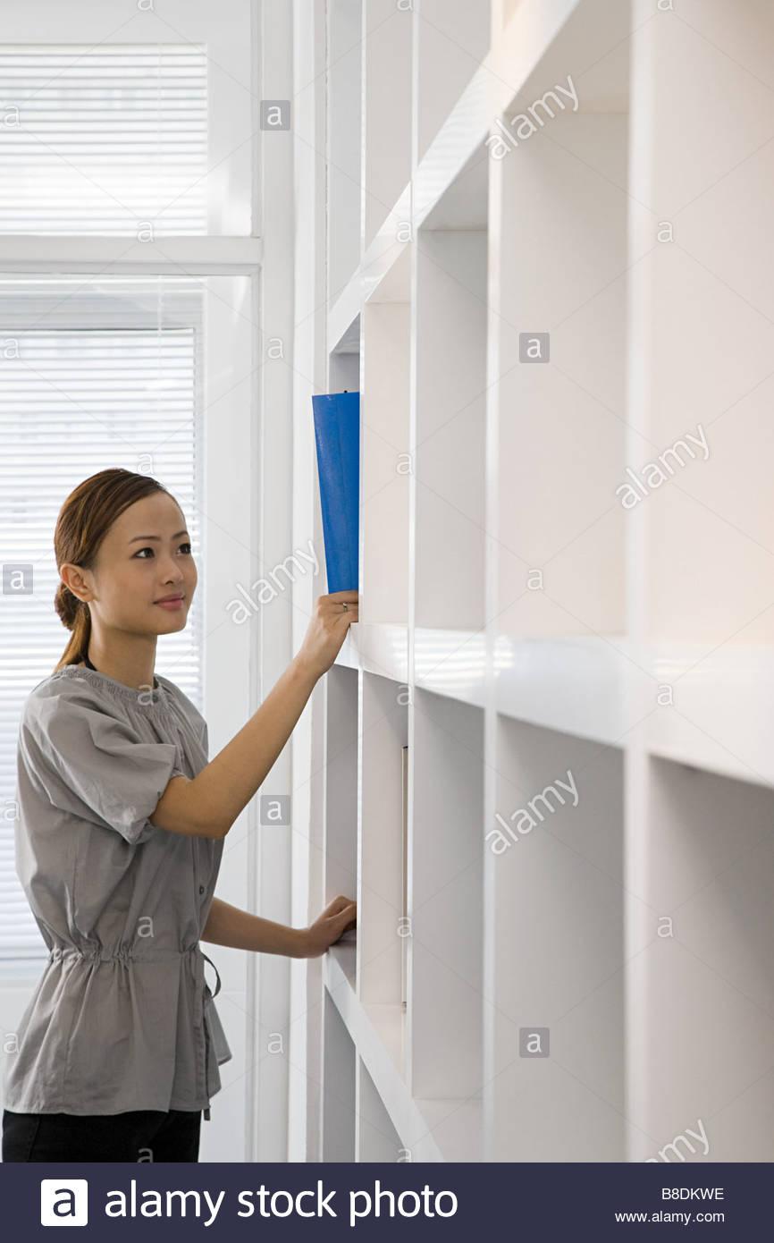 Woman by bookshelf - Stock Image