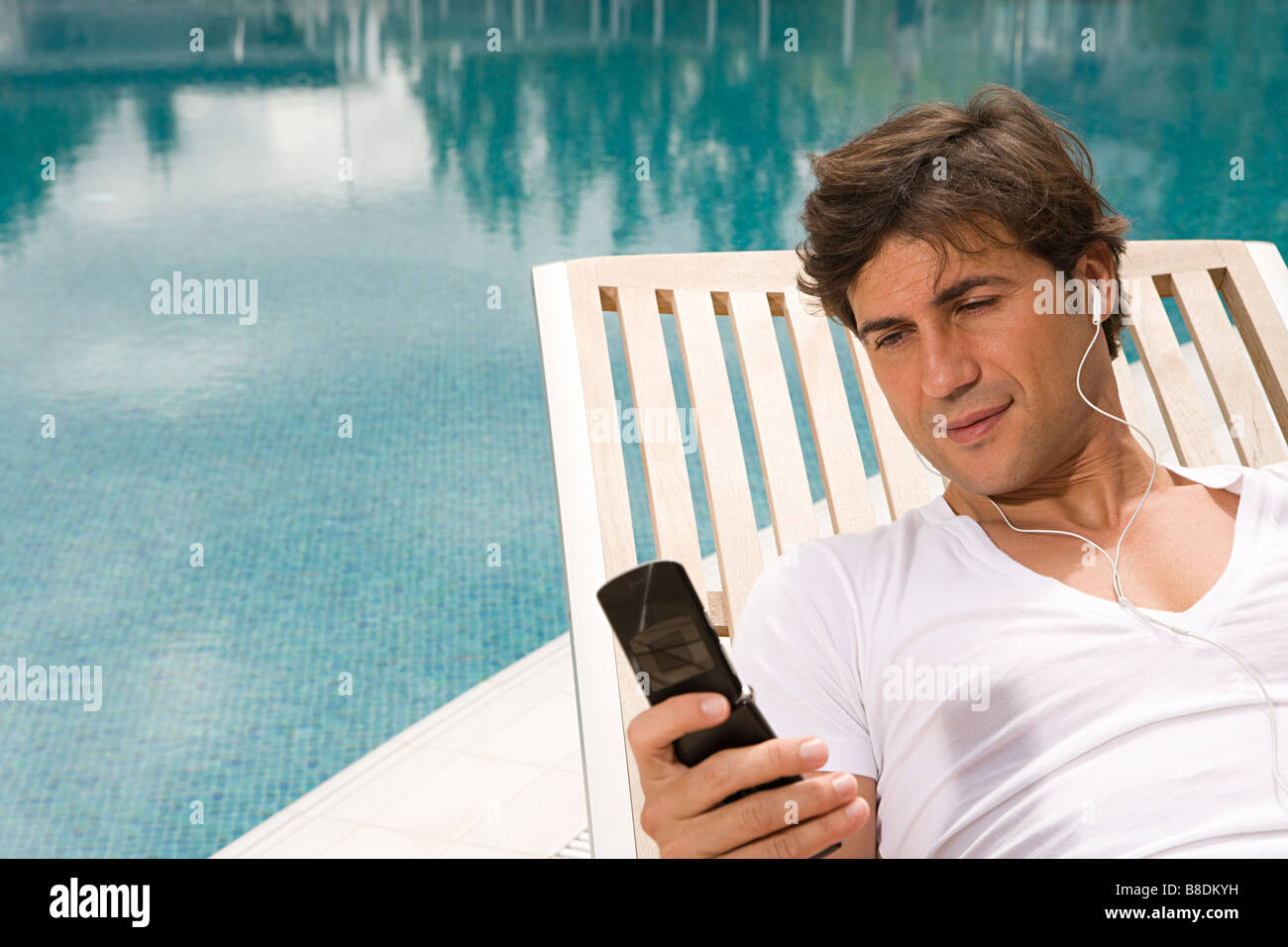 Man listening to music on cellular phone - Stock Image