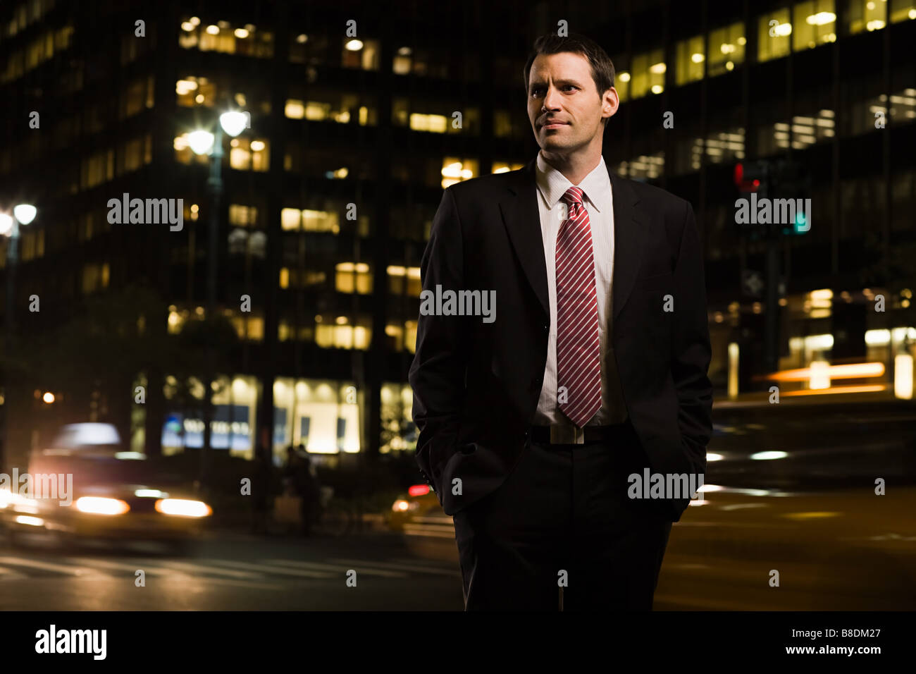 Businessman standing near a busy road - Stock Image