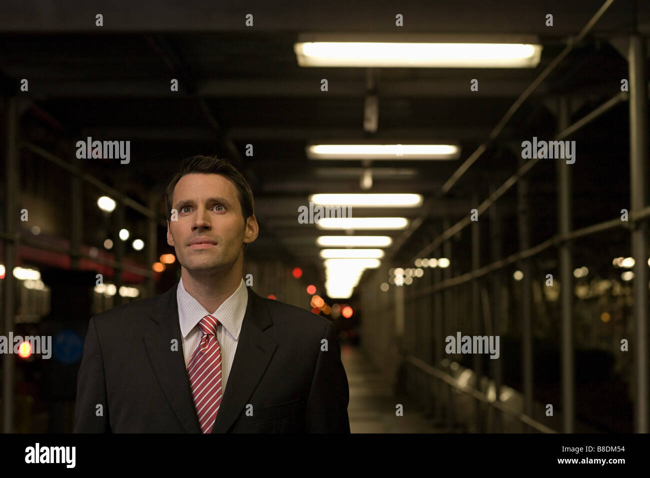 Stunned looking businessman in a walkway - Stock Image