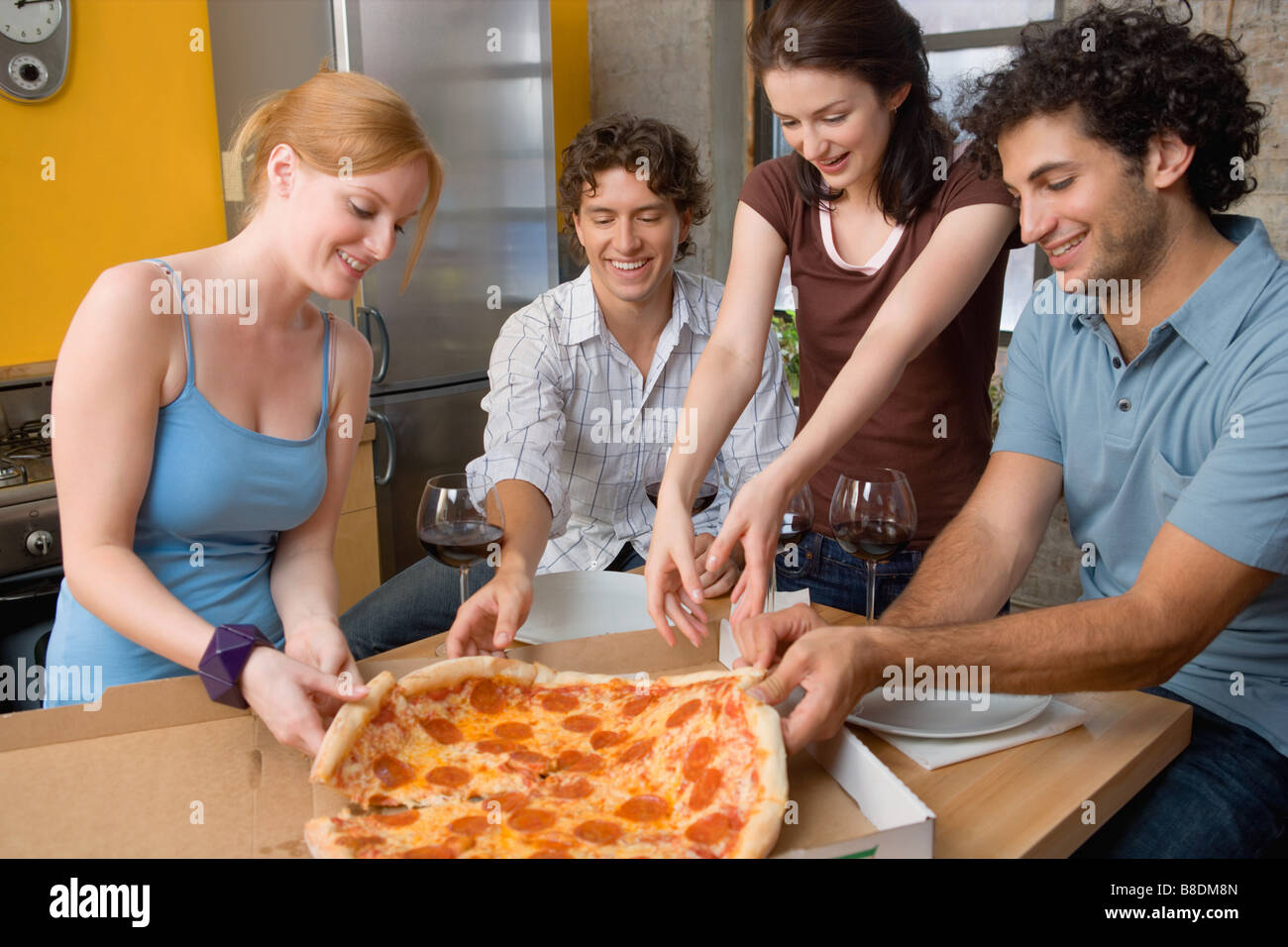 Friends sharing a pizza Stock Photo