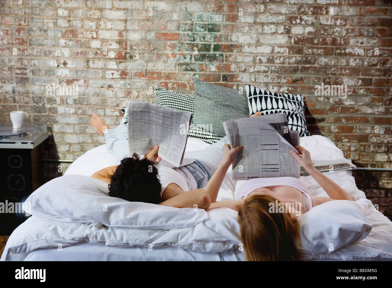 Couple reading newspapers in bed - Stock Image