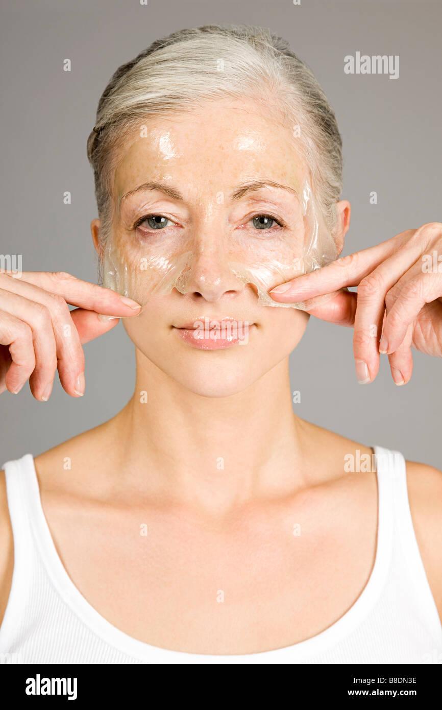 Woman with anti-aging face mask - Stock Image