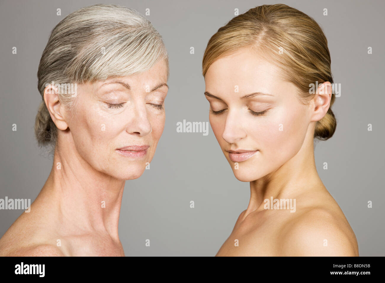 Young and senior women with eyes closed - Stock Image