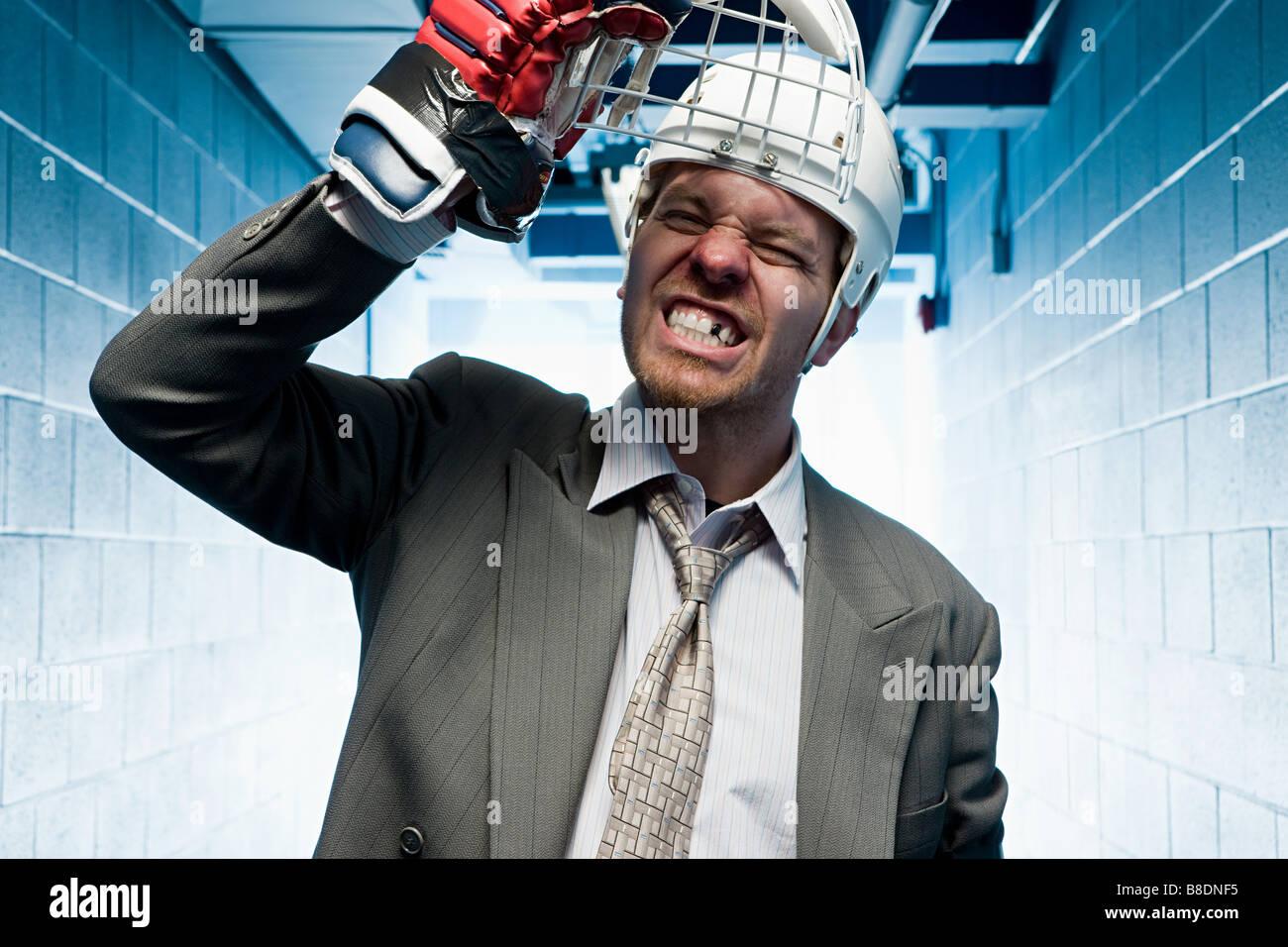 Grimacing businessman in a sports helmet - Stock Image