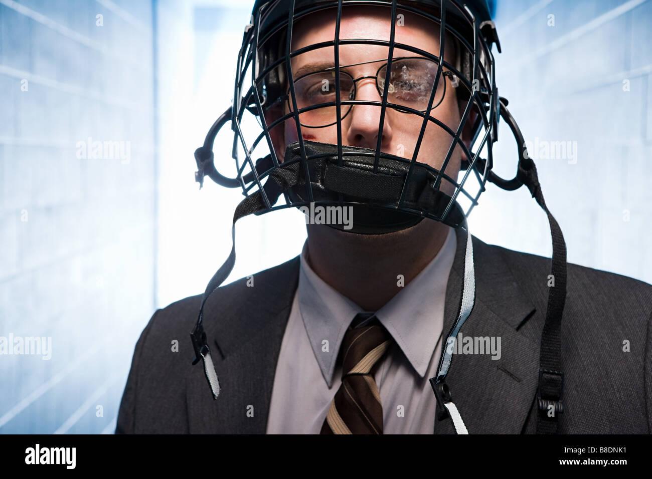 Injured businessman wearing an ice hockey helmet Stock Photo