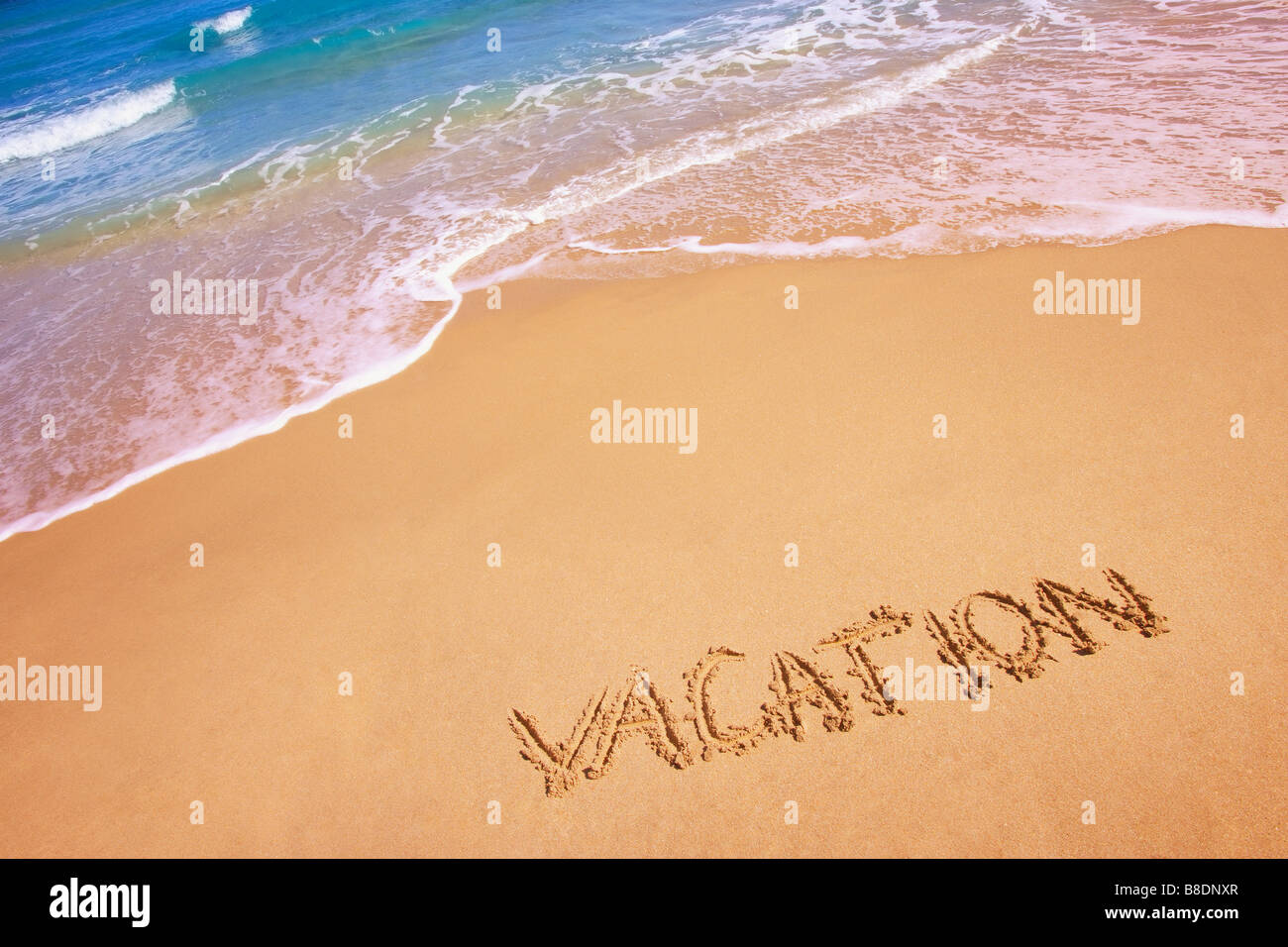 Vacation written in the sand Stock Photo
