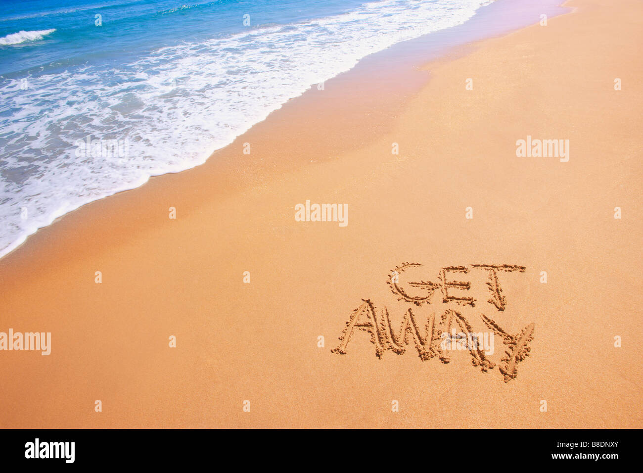 Get away written in the sand - Stock Image