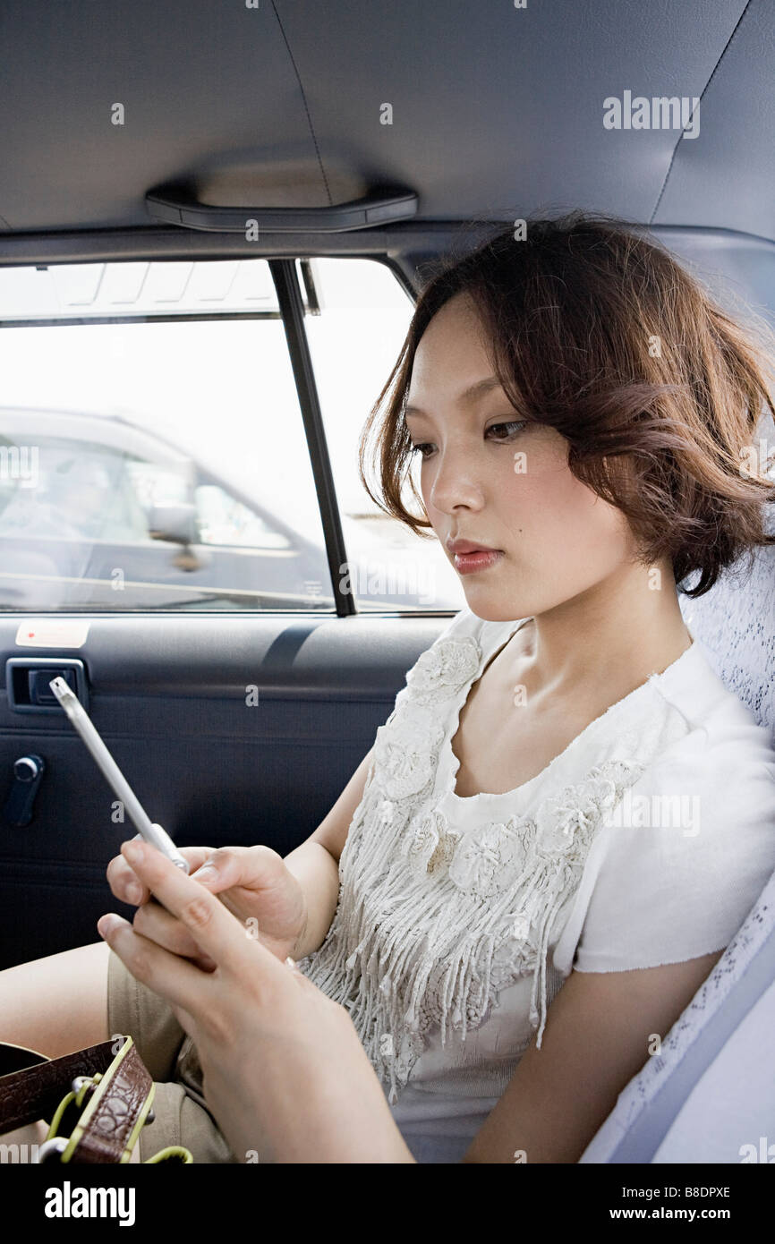Young woman in cab with cellphone - Stock Image