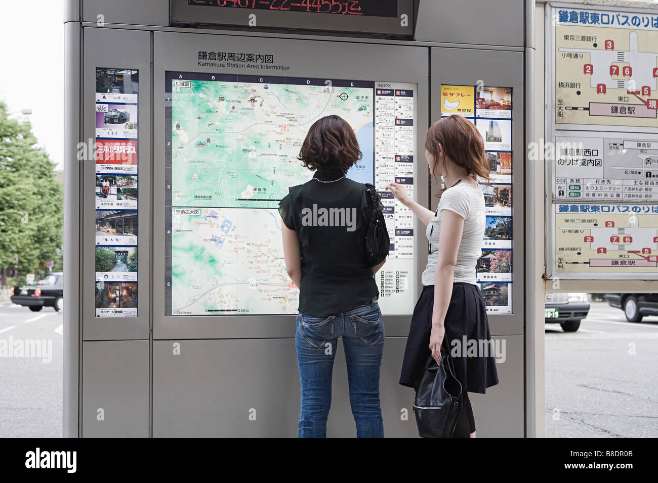 Friends looking at map - Stock Image