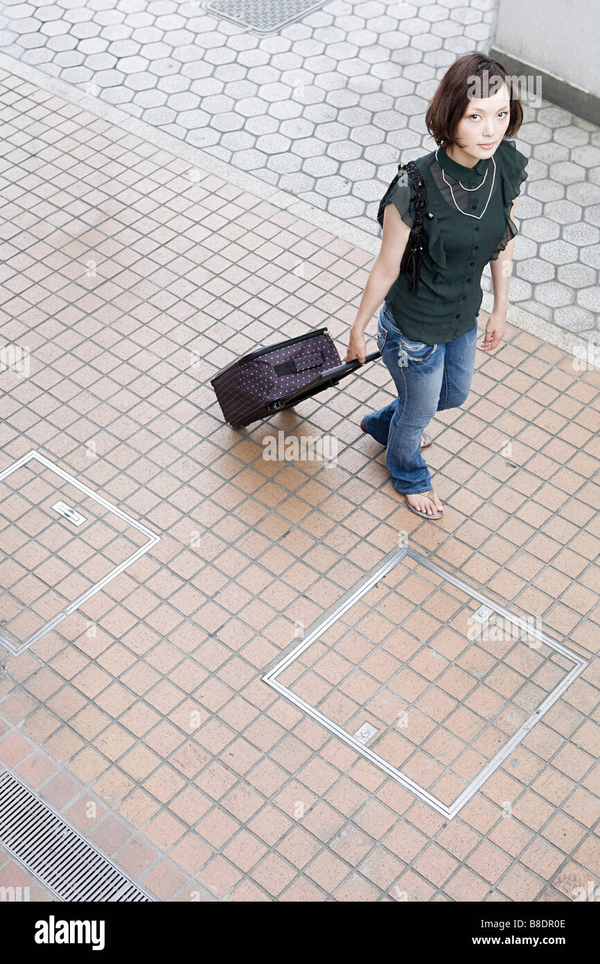 Young woman with suitcase - Stock Image