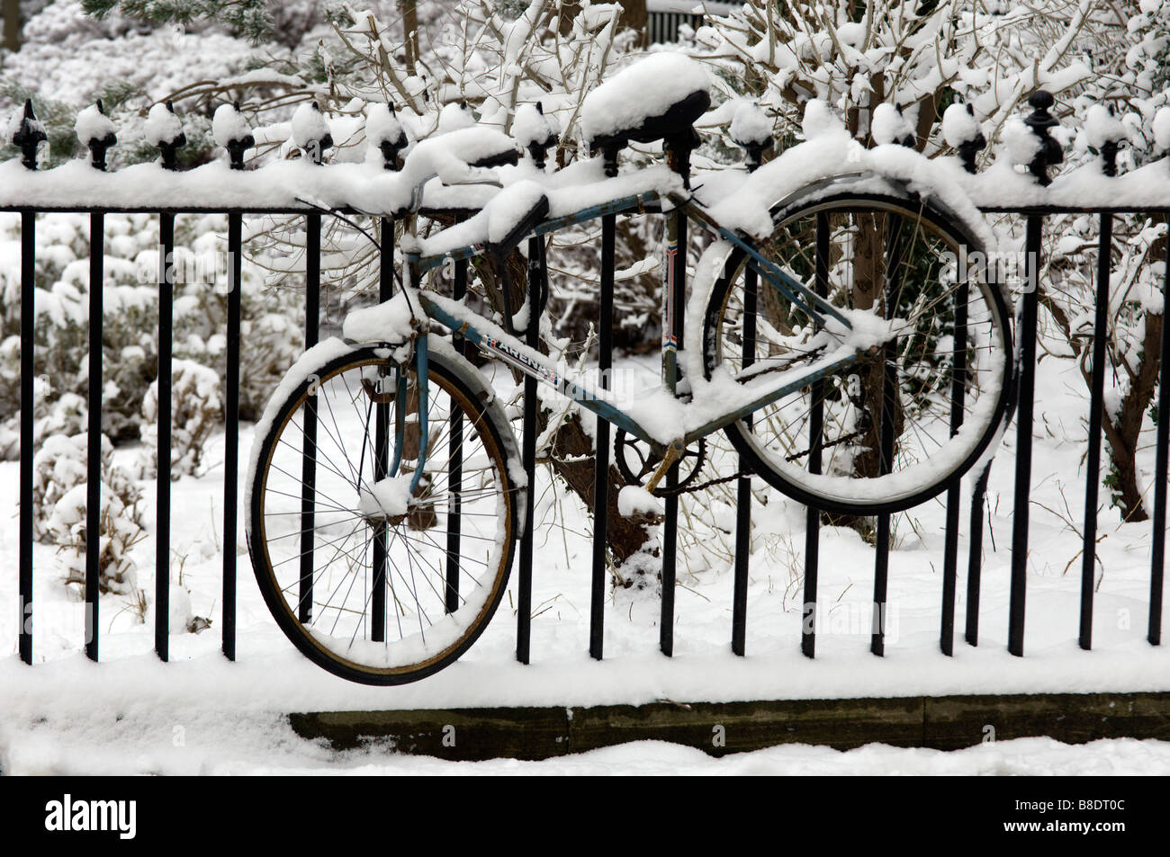 A bicycle covered in snow tethered to Victorian railings in Brunswick Square Hove East Sussex - Stock Image