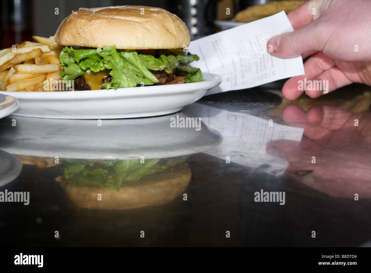 restaurant employee selling a cheese burger ticket - Stock Image