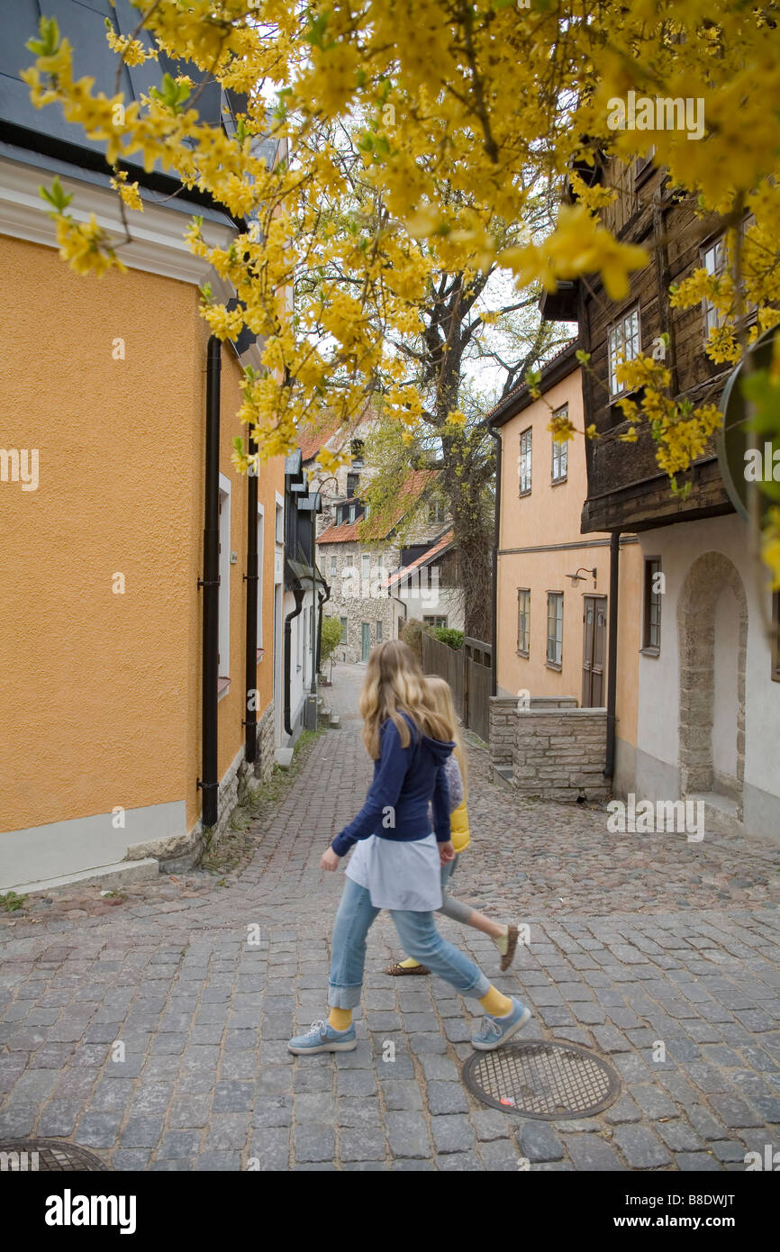 A girl crossing the tiny street in Visby the capital of the Gotland island Sweden - Stock Image