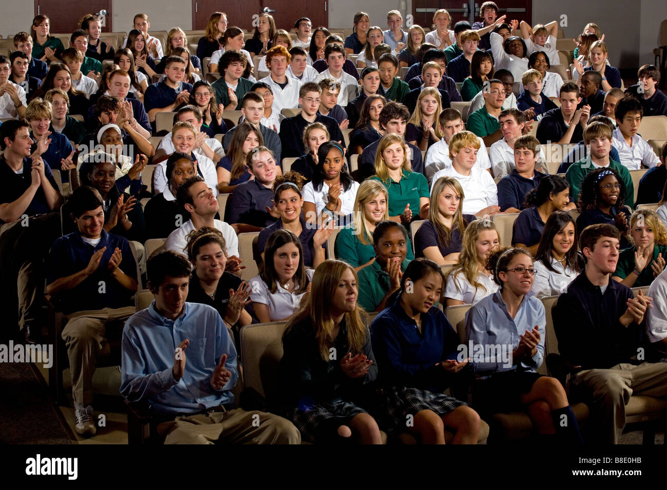 High school and middle school students seated in an auditorium. - Stock Image
