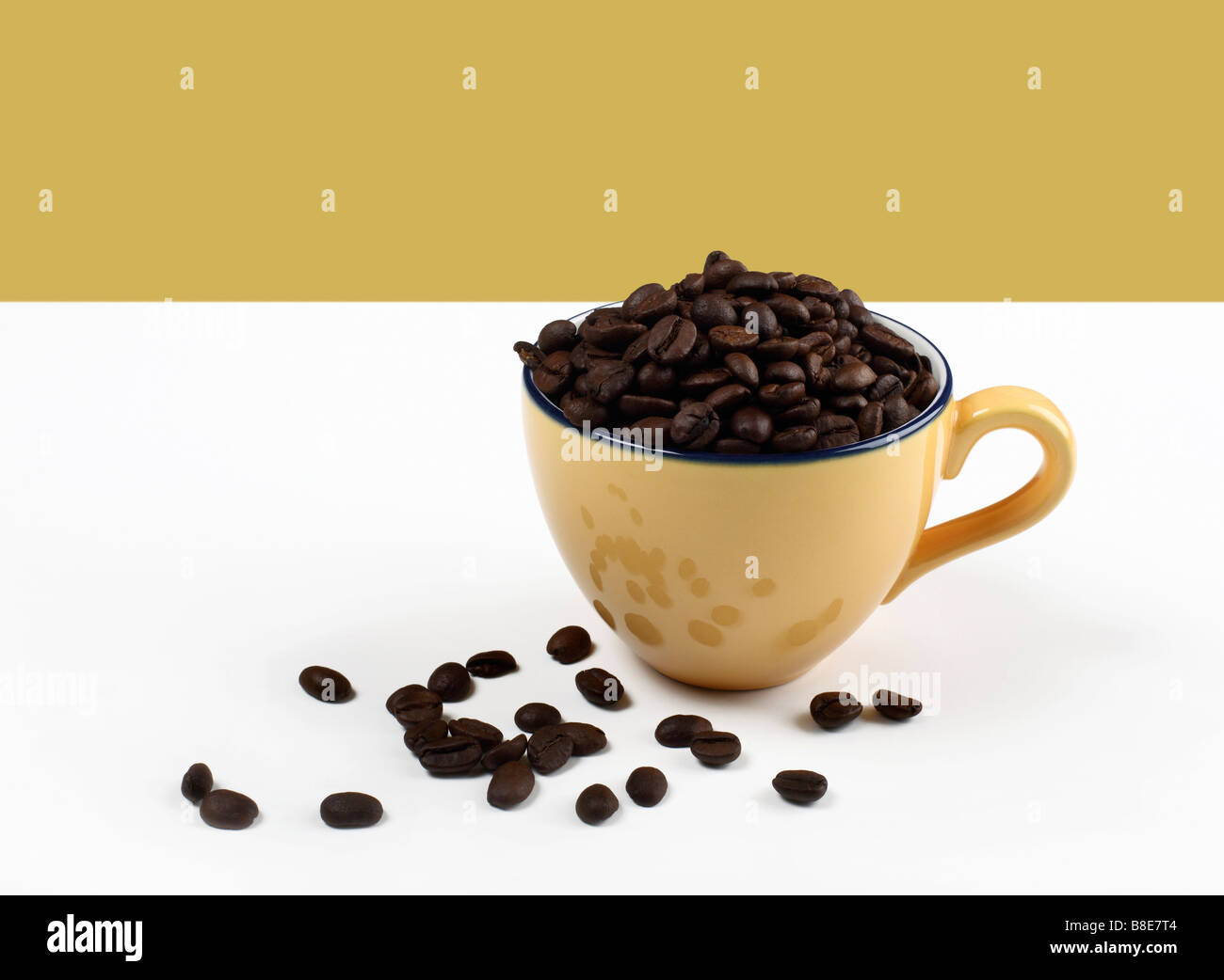 Coffee cup filled with coffee beans - Stock Image