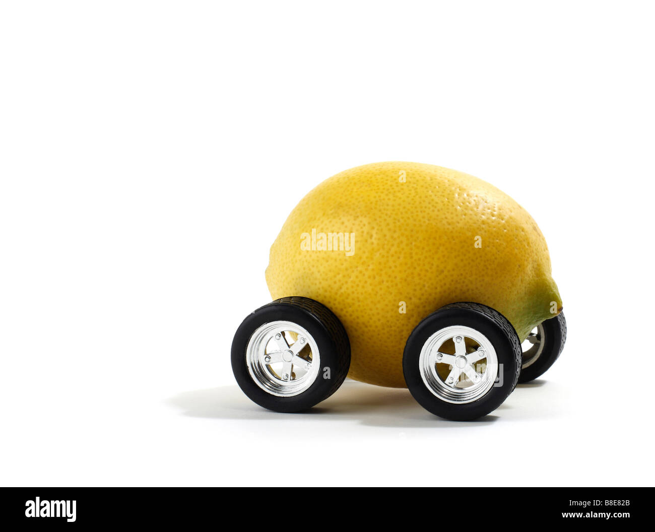 Studio shot of a lemon with automobile wheels - Stock Image