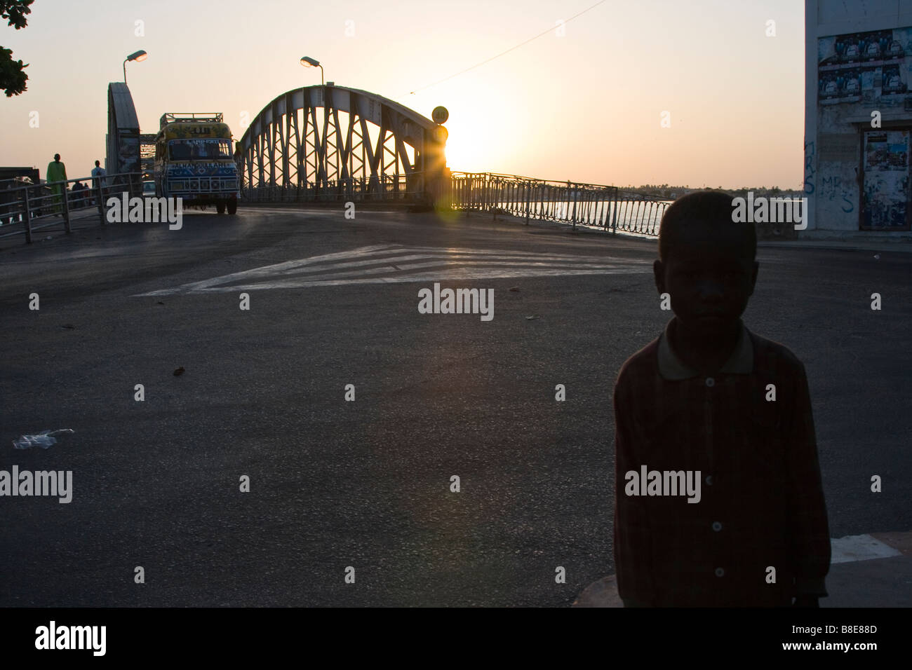 Homeless Boy in front of Pont Faidherbe in St Louis in Senegal West Africa - Stock Image
