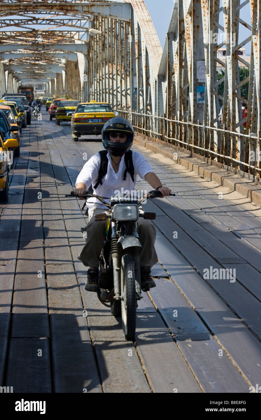 Foreign Tourist Riding a Motorcycle Across the Faidherbe Bridge in St Louis in Senegal Africa - Stock Image