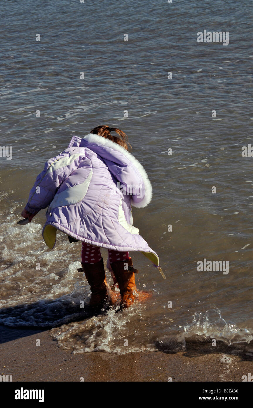 Young girl dodging waves at beach - Stock Image