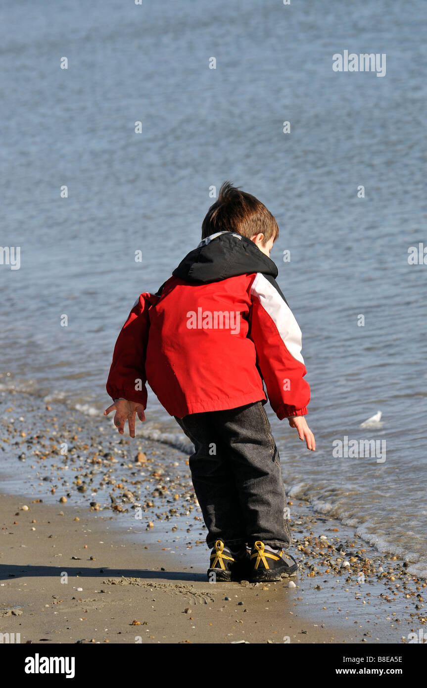 Young boy at Salty Brine beach in Rhode Island dodging waves. - Stock Image