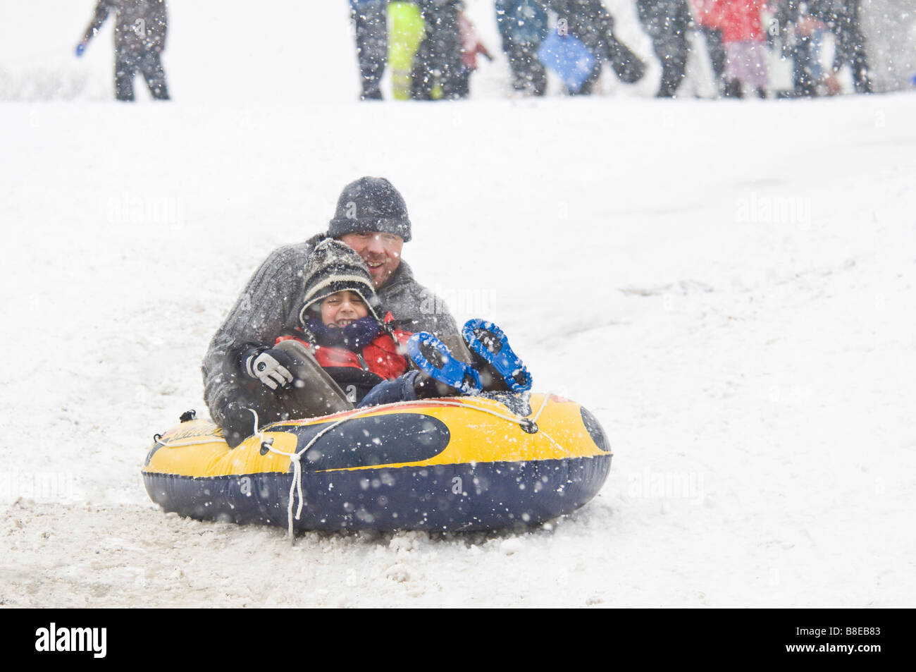 A father and son make novel use of an inflatable boat as an improvised sledge in Greenwich Park during snowfall. - Stock Image