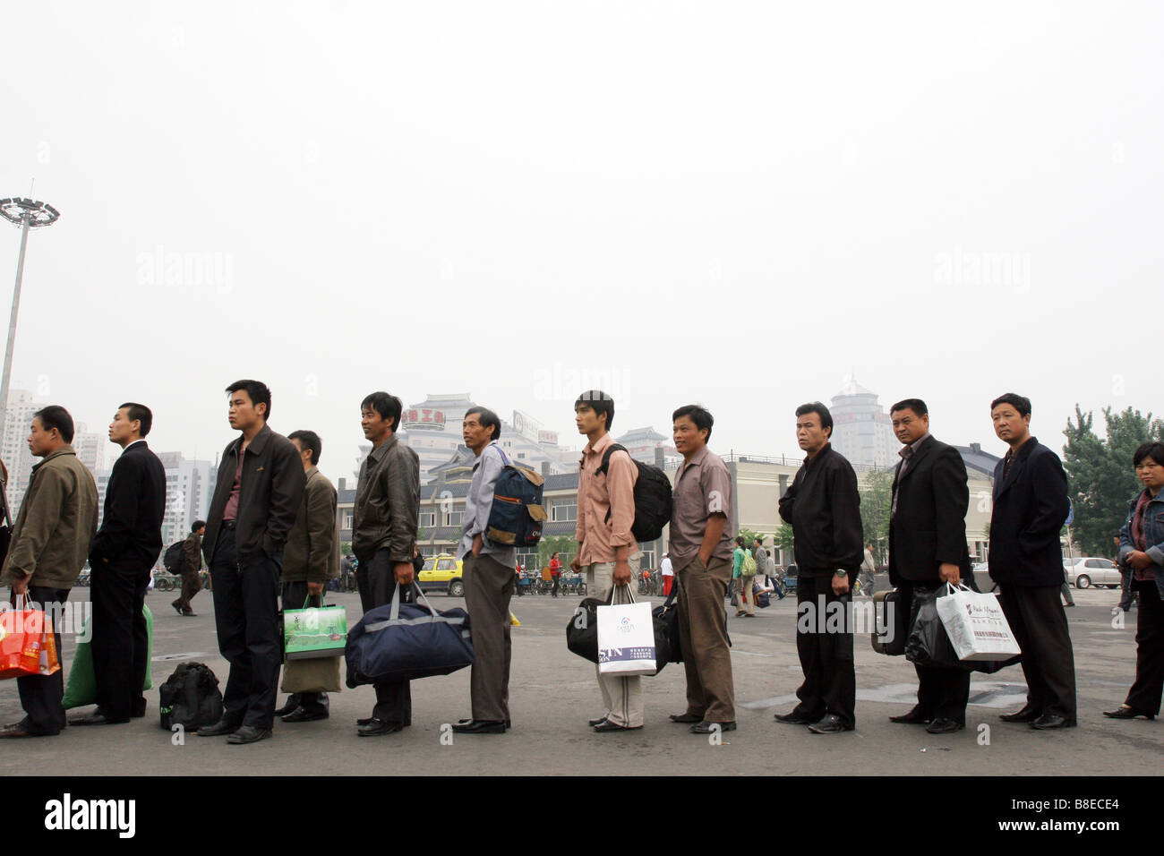 Forming a line / queue waiting for a bus in Beijing, China - Stock Image