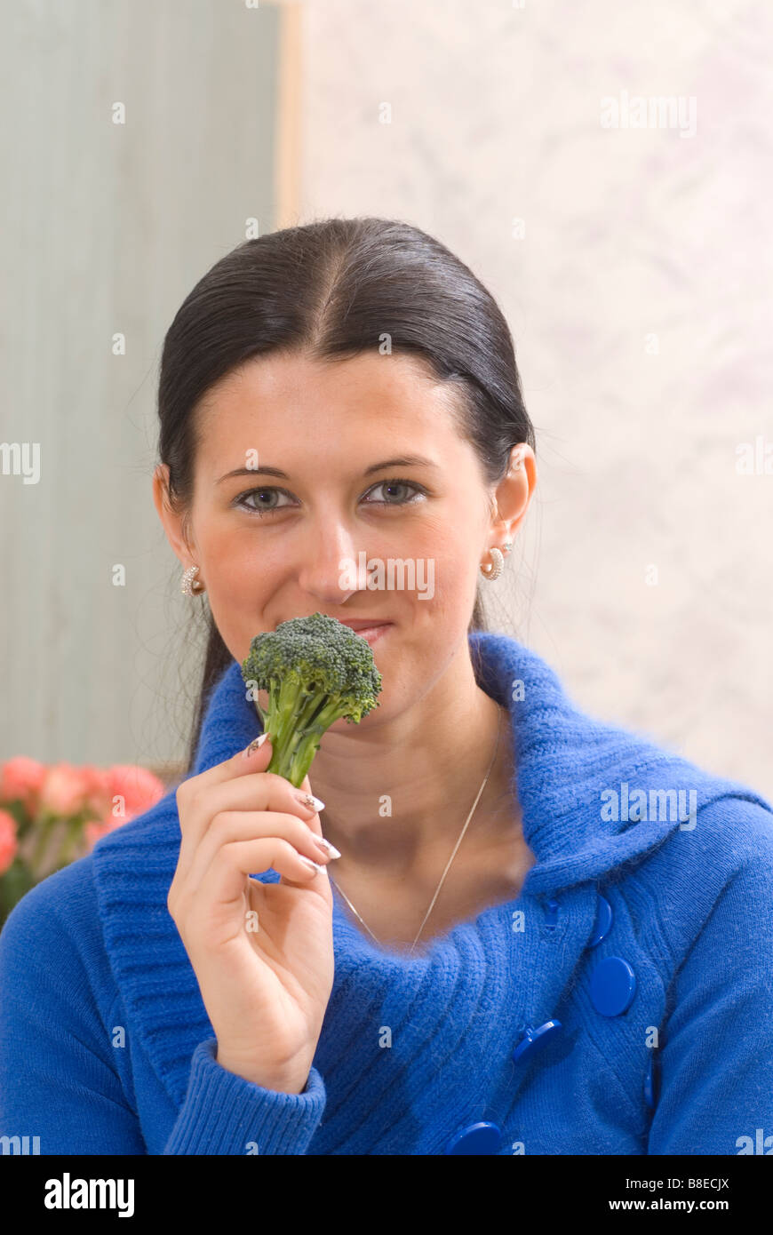 Young woman eating green raw broccoli - Stock Image