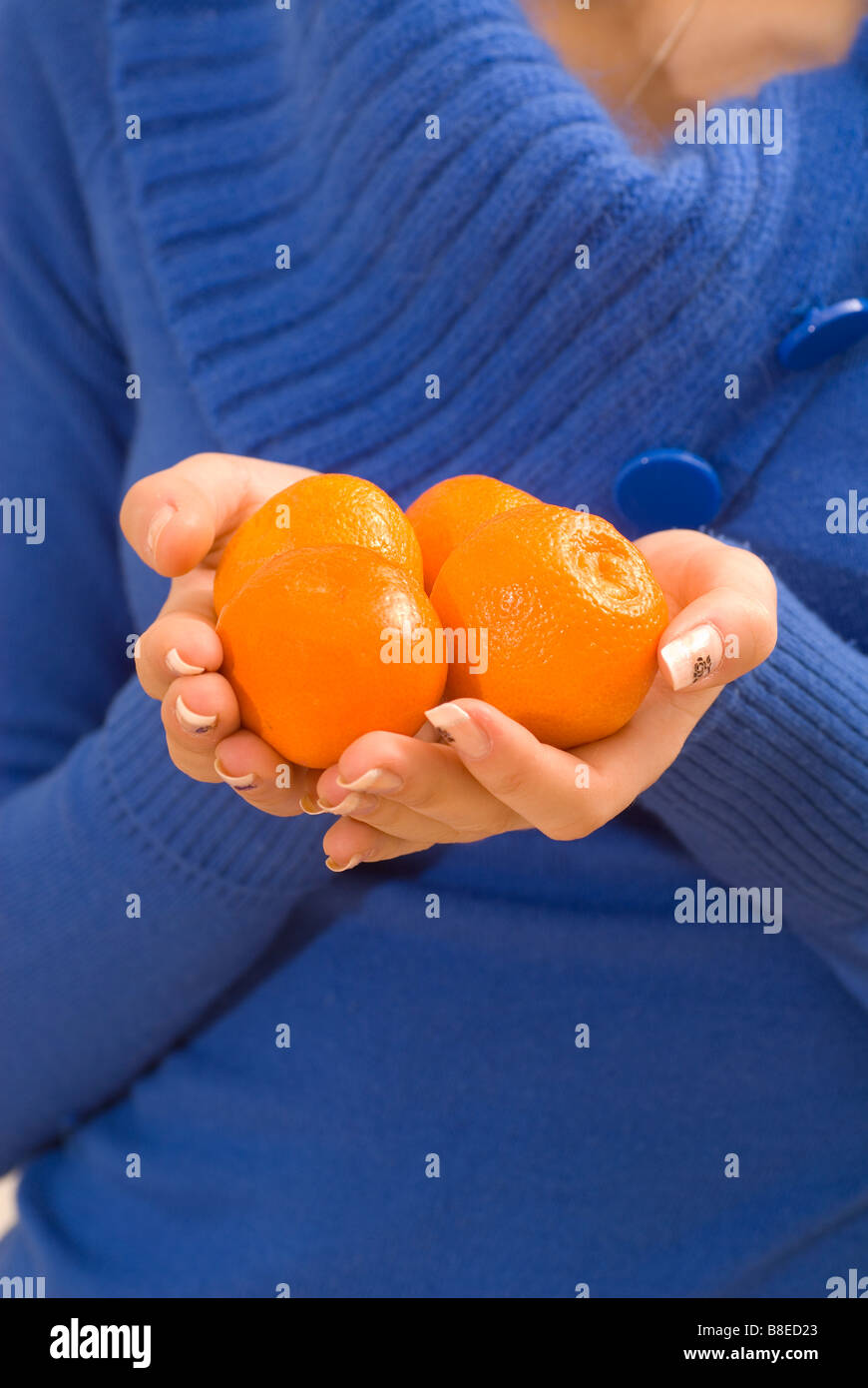 Close up of woman's hands holding mandarin fruits - Stock Image
