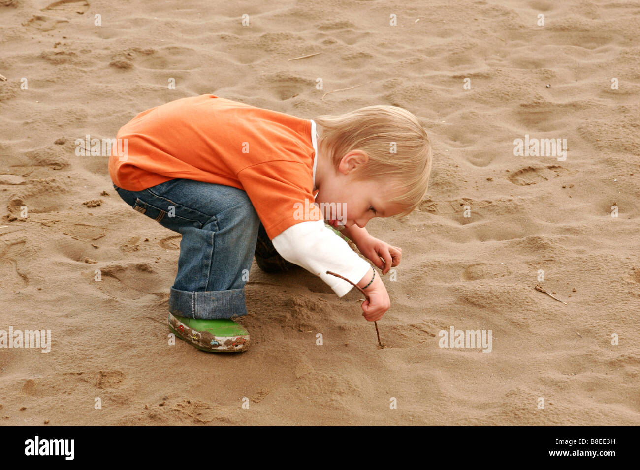2 year old boy using a stick to draw in the sand at the beach - Stock Image