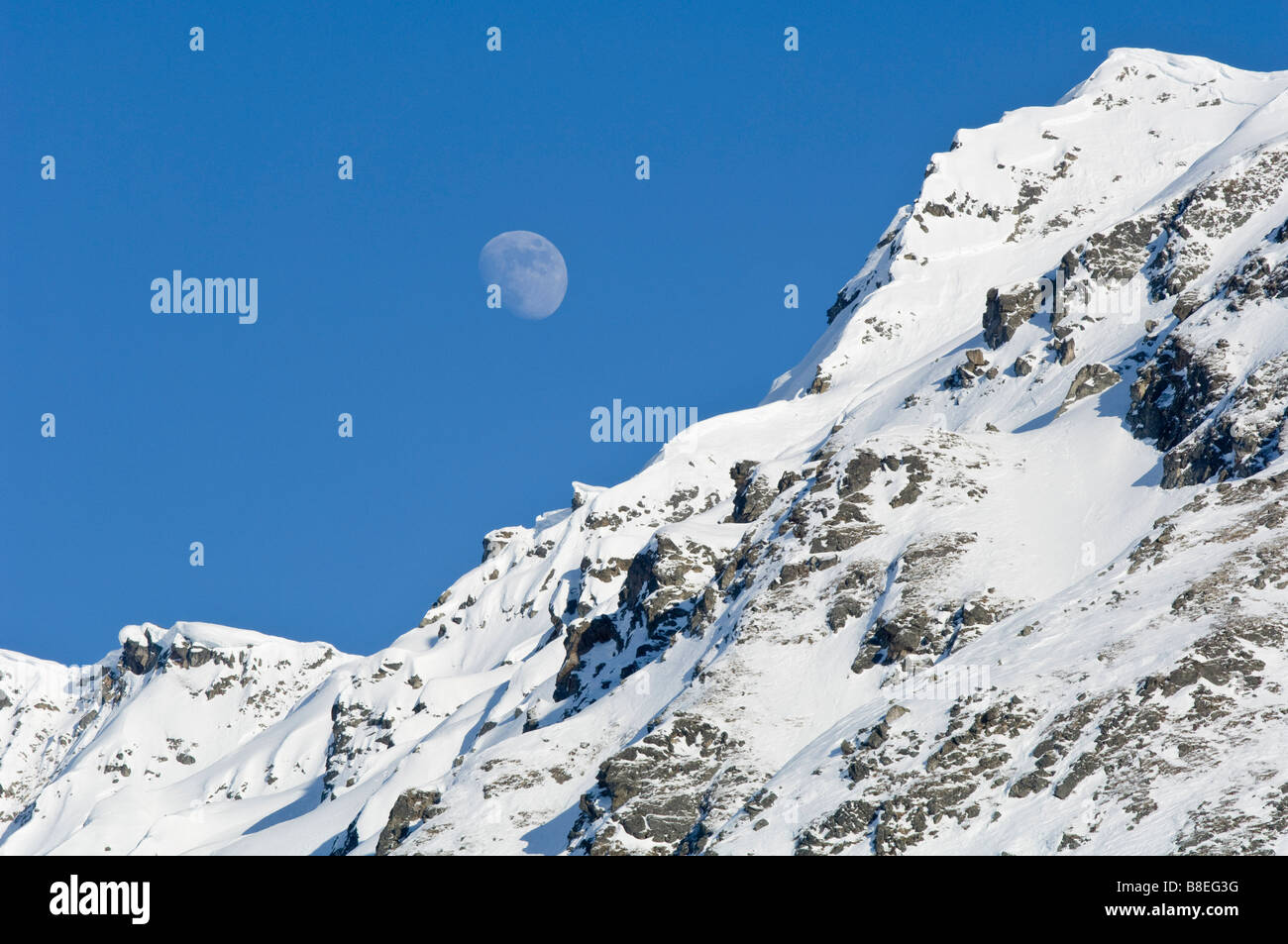 Moon rising over snow covered mountain peak at Hatcher Pass in Southcentral Alaska - Stock Image