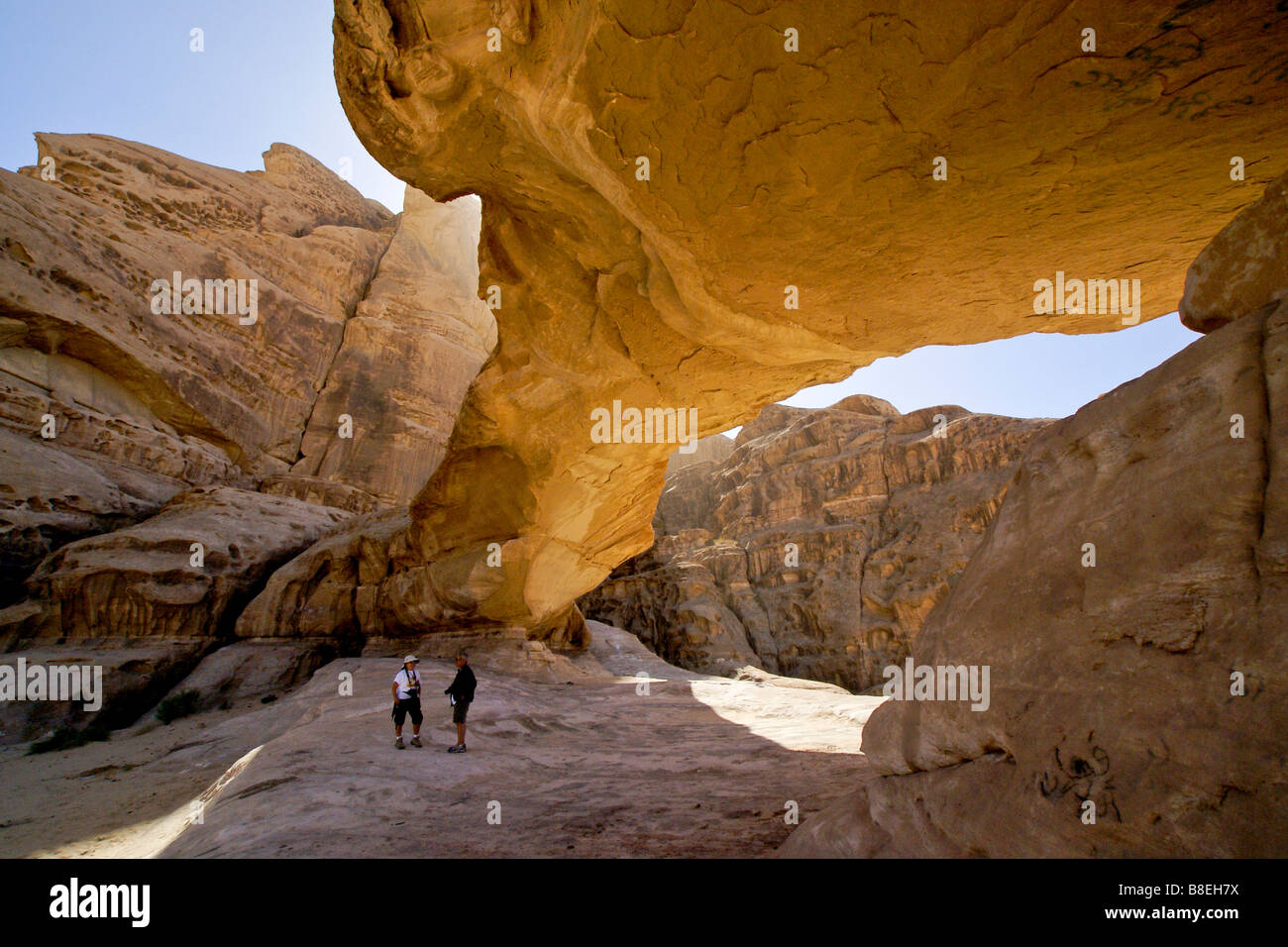 Hikers under natural arch, Wadi Rum, Jordan - Stock Image