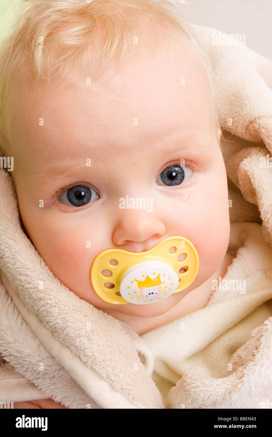 Tearful suckling baby 7 months old with yellow dummy - Stock Image