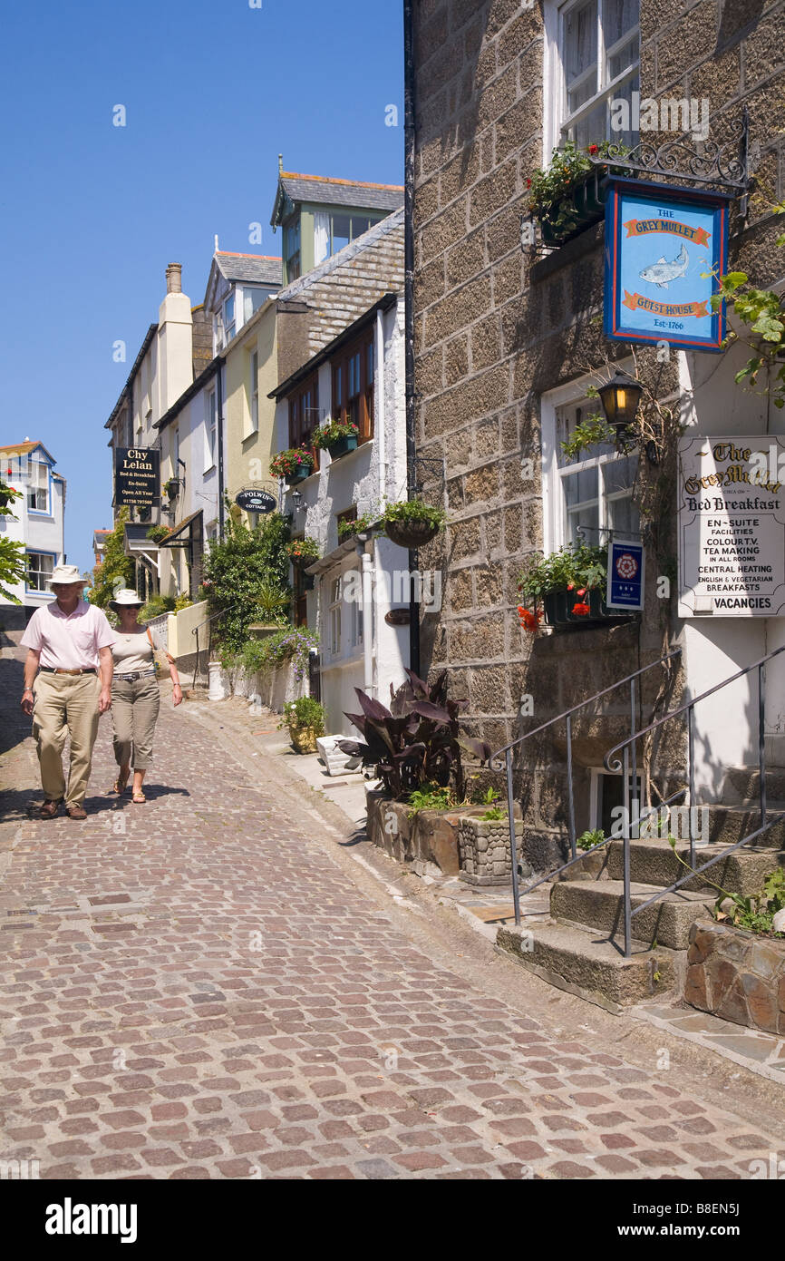 Couple stroll down side streets in summer sun St Ives Cornwall West Country England UK United Kingdom GB Great Britain - Stock Image
